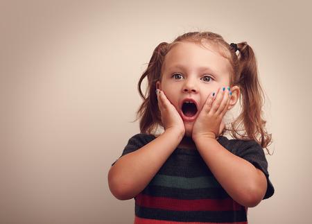 bambini: Carino sorprendente ragazza bambino con la bocca aperta e la mano vicino al viso a guardare copia spazio vuoto. Vintage ritratto