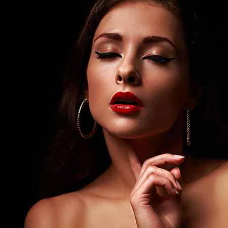 Beautiful makeup female model with red lips and black eyeliner. Closeup on black background photo