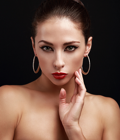 Closeup portrait of beautiful female perfect makeup face looking on black background photo