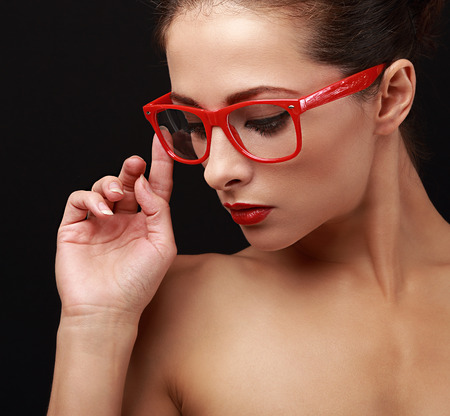 Beautiful makeup woman in red eyes glasses looking down. Closeup portrait on black photo