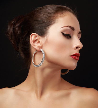 Beautiful woman face profile in fashion earrings with elegant hairstyle on dark black background Stock Photo