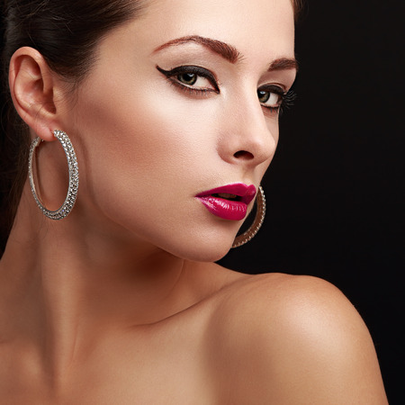 Sexy female model face. Closeup. Bright makeup. Pink lips and black eyeliner. Black background photo