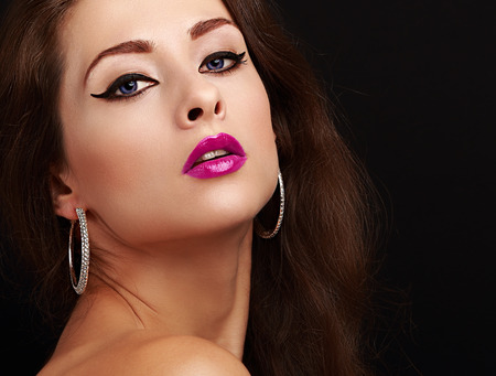 Bright sexy makeup with black arrows and bright pink lips. Closeup portrait photo