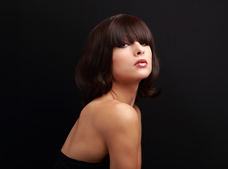 Beautiful makeup woman with short hair style posing on black background with empty copy space photo