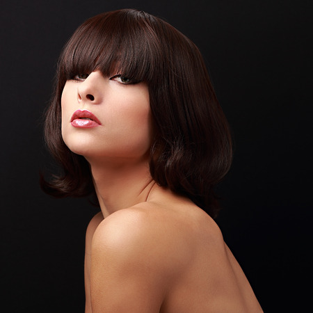 Beautiful woman with short hair and bob posing. Closeup portrait on black photo