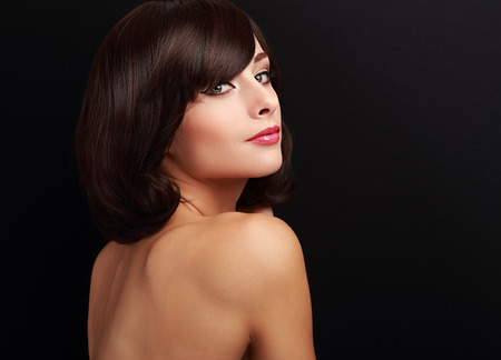 Beautiful smiling makeup woman with short hair looking on black background photo