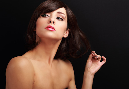 Beautiful thinking makeup woman holding the hand short hair and looking on black background photo