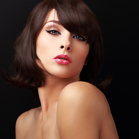 Sexual makeup woman with red sexy lips and short brown hair looking. Closeup portrait on black background photo
