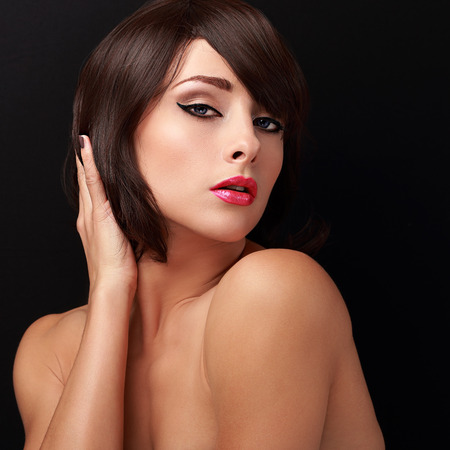 Sexy brunette woman with bright makeup, red lips and short hair style looking on black background photo