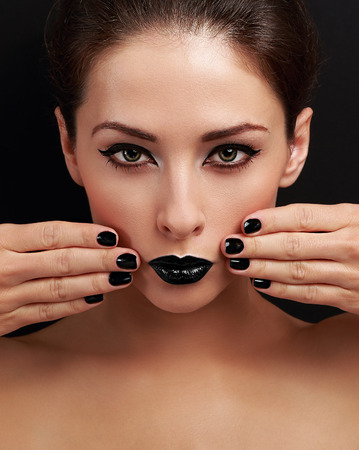 Beautiful bright evening makeup woman, black nails polish and black lipstick looking serious on black background photo