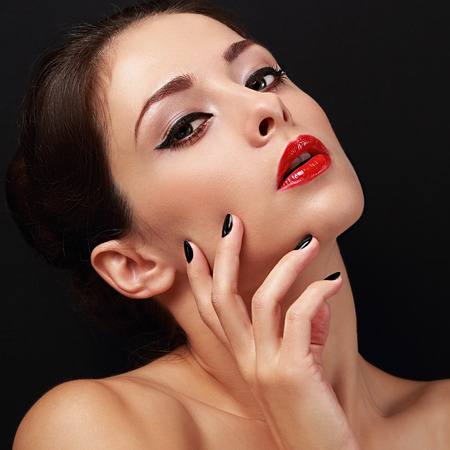 Sexy makeup female glamour model with red lipstick and black polish finger nails on black background. Closeup photo