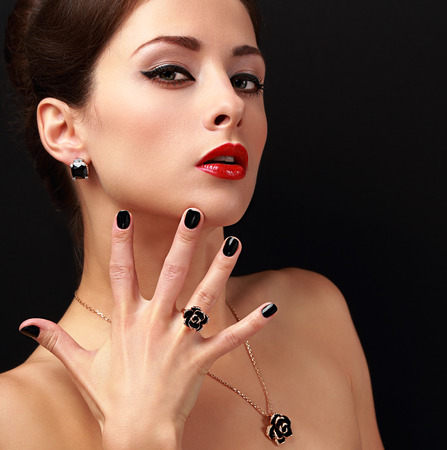 Beautiful fashion model with jewelry accessories and black fingernail looking sexy. Red lips makeup. Closeup photo