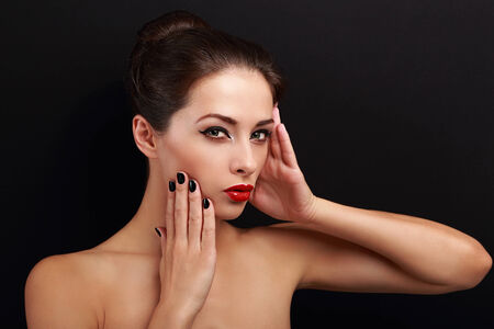Sexy makeup female model posing with red lipstick on black background photo