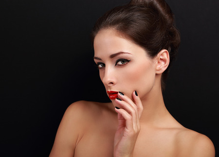 Sexy flirting female model with red lipstick and fingers near lips looking on black background photo