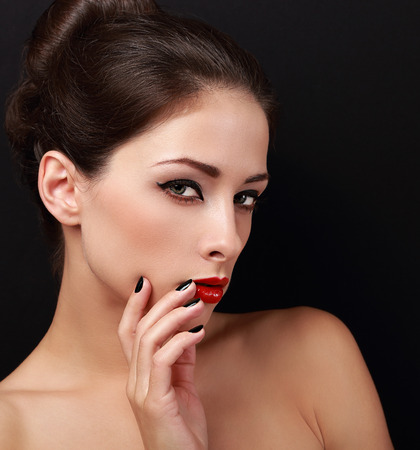 Sexy style makeup woman looking with bright red lips. Closeup portrait on black background photo