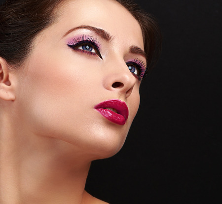 Chic woman face makeup. Long lashes and gloss lipstick. Closeup on black background photo