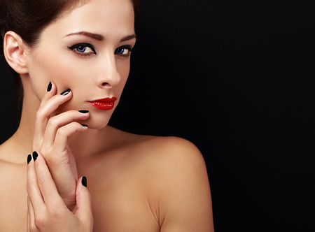 Happy makeup woman looking with red lips and black fingers on black background photo