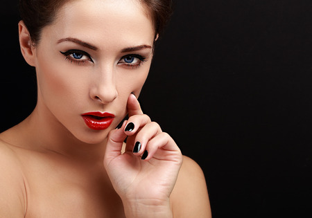 Beautiful sexy woman portrait. Black eyeliner, red lipstick and black nails polish looking with empty copy space background photo