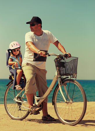 Father and daughter biking on the beach on blue sea background photo