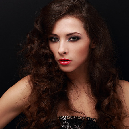 Fashionable famale model with smokey eyes makeup and curly hair style on black background. Closeup portrait photo