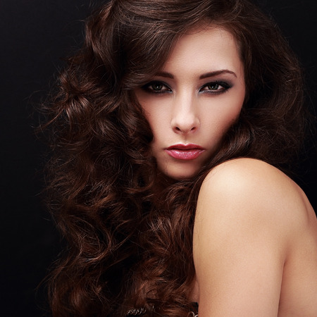 Sexy bright makeup female model with brown curly hair. Closeup portrait photo