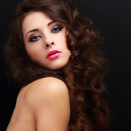 Beautiful makeup woman with curly hair style looking sexy with pink lipstick on black background photo