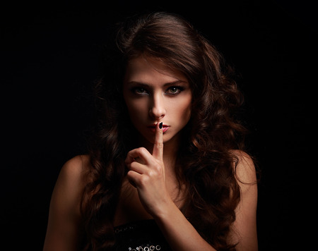 Beautiful make-up woman showing silence sign the finger near lips on black background Foto de archivo
