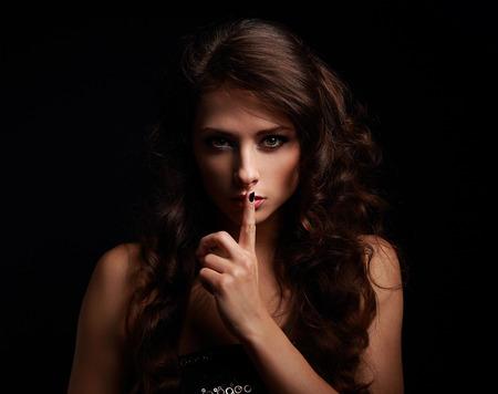 mujer sexy: Hermosa mujer de maquillaje que muestra la muestra del silencio con el dedo cerca de los labios sobre fondo negro