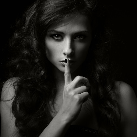 Serious woman gesture quiet sign in dark shadows. Closeup portrait. Black and white