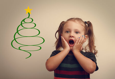 surprising: Funny surprising kid girl looking on fur tree illustration with open mouth. Vintage portrait Stock Photo
