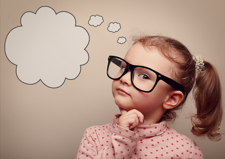 Smart kid in glasses thinking with speech bubble above with empty copy space. Vintage portrait