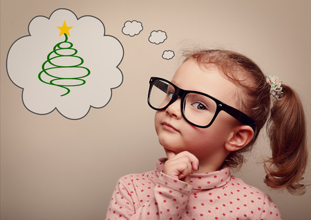 Cute kid girl in glasses thinking about gift on Christmas holiday. Vintage portrait photo