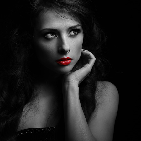 Beautiful makeup woman looking dramatic with red lipstick in darkness. Black and white portrait photo