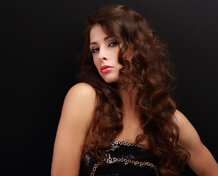 Beautiful chic woman with curly hair style looking sexy on black background photo