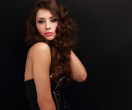 Sexy fashion female model in modern black dress posing on black background photo