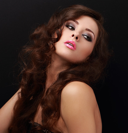 Sexy hot bright makeup woman with long hair looking. Closeup portrait on black background photo