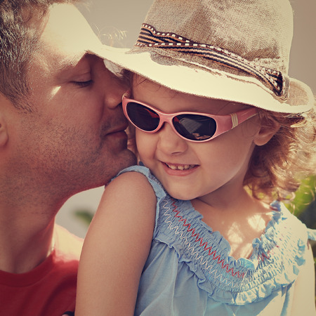 Happy father kissing his daughter in fashion glasses and hat outdoors photo