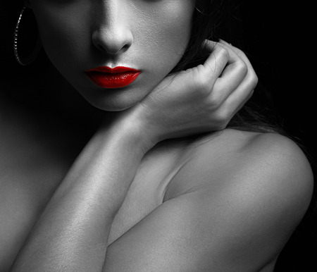 Black and white art portrait of sexy woman with red glossy lips on dark. Closeup photo