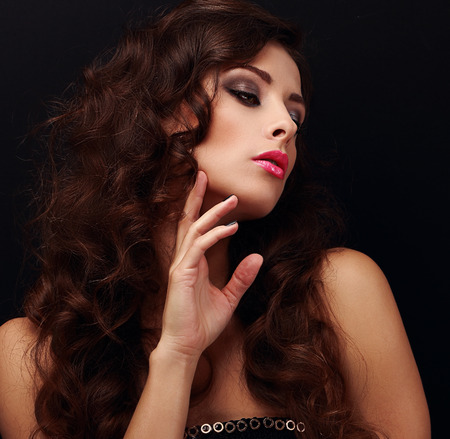 Elegant curly hair woman looking. Bright model with smokey eyes makeup on black background. Closeup photo