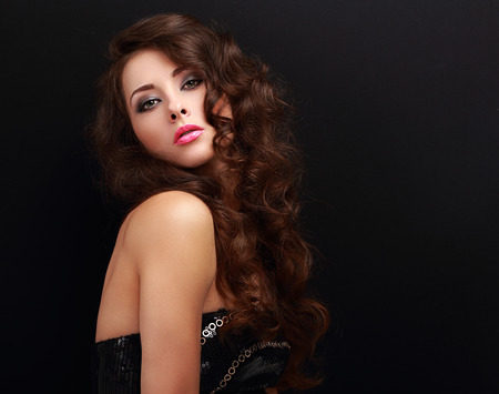 Sexy bright makeup woman with long curly hair posing on black background with empty copy space photo