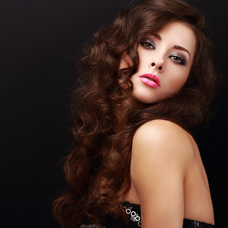 Beautiful makeup woman with curly hair looking on black. Closeup portrait photo
