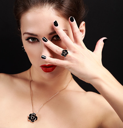 Sexy makeup model with black nails gloss looking. Closeup portrait on black background photo