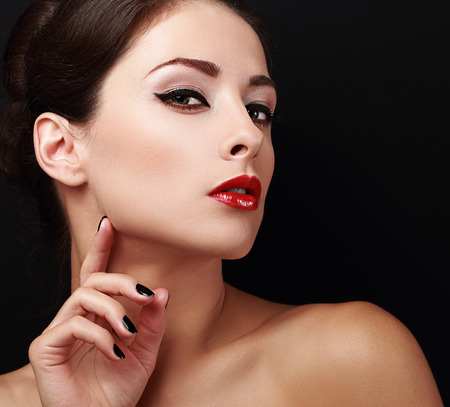 skin color: Perfect makeup woman face with red lips and black nails on black background. Closeup portrait