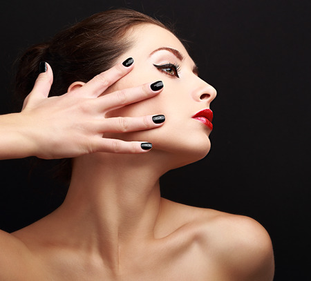Sexy makeup woman with black nails on face. Woman profile with red lipstick photo