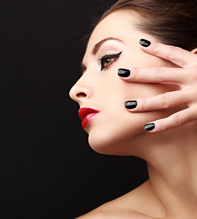 Woman perfect makeup profile with black nails polish on black background. Closeup portrait photo