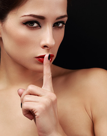 Sexy makeup woman showing shh the finger near red lips and looking serious on black background. Closeup portrait photo