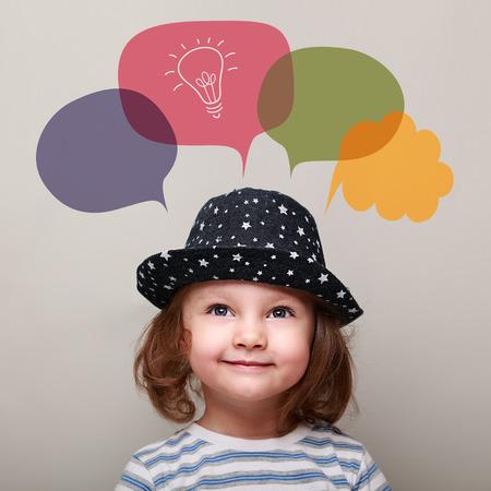 bambini pensierosi: Bambino felice pensando e alzando lo sguardo su lampadina idea in bolla su sfondo grigio. Ritratto del primo piano