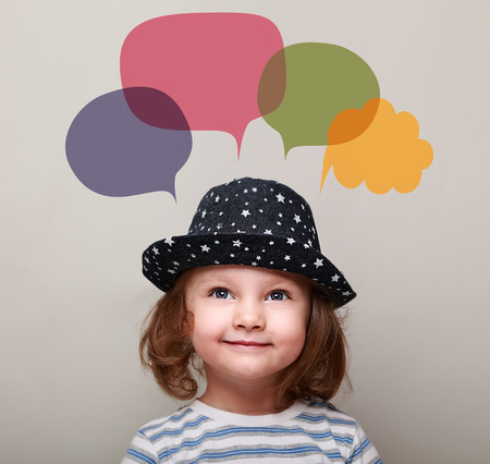 Cute happy kid in hat girl thinking and looking up on colorful bubbles above on grey background