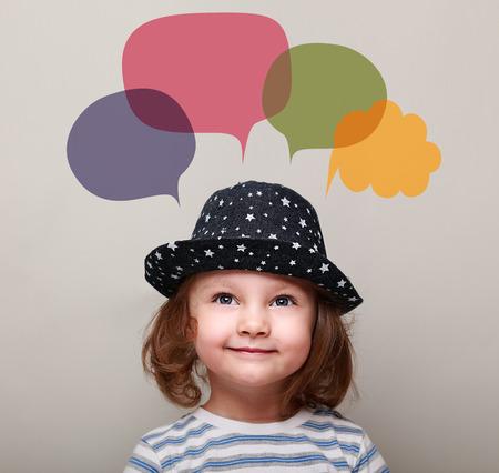 Niño feliz lindo en pensamiento chica sombrero y buscar en las burbujas de colores por encima sobre fondo gris Foto de archivo - 36109365