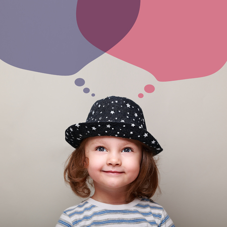 creative brain: Thinking small kid dreaming about with big bubbles above on grey background